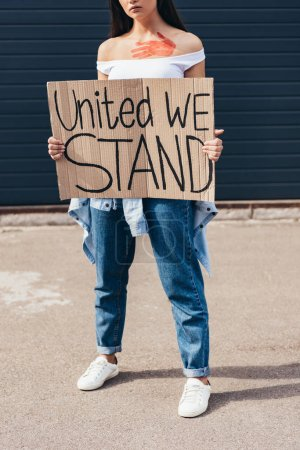 Photo for Cropped view of feminist holding placard with inscription united we stand on street - Royalty Free Image