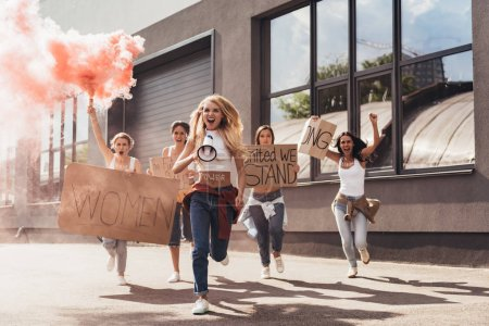 Photo for Full length view of screaming multiethnic feminists with loudspeaker holding placards with slogans and running on street - Royalty Free Image