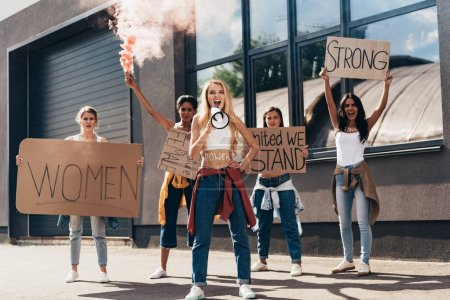 Photo for Full length view of screaming multiethnic feminists with loudspeaker holding placards with slogans on street - Royalty Free Image