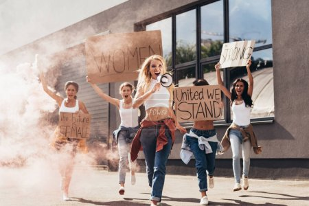 Photo for Full length view of screaming feminists with loudspeaker holding placards with slogans and running on street - Royalty Free Image