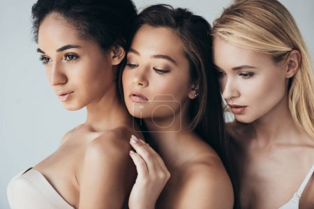 Photo pour Three sensual multiethnic young women embracing isolated on grey - image libre de droit