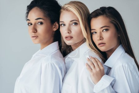 Photo for Three attractive multiethnic girls in white shirts embracing isolated on grey - Royalty Free Image