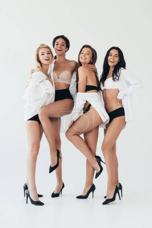 Photo pour Full length view of four smiling sexy multiethnic girls wearing white shirts and heels on grey - image libre de droit