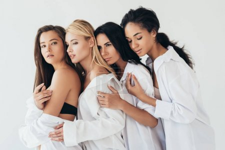 Photo pour Four attractive multiethnic women in white shirts embracing isolated on grey - image libre de droit