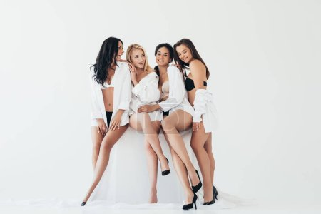 Photo for Four smiling sexy multiethnic girls wearing white shirts and heels sitting isolated on grey - Royalty Free Image