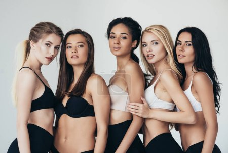 Photo pour Five sexy multiethnic young women in underwear embracing isolated on grey - image libre de droit