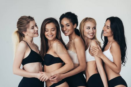 Photo for Five sexy multiethnic young women in underwear embracing and smiling isolated on grey - Royalty Free Image