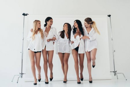 Photo for Full length view of five sexy multiethnic girls wearing white shirts and heels smiling on grey - Royalty Free Image