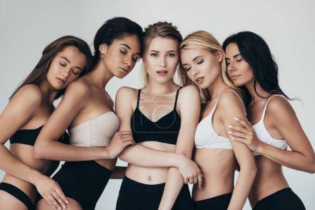 Foto de Cinco chicas multiétnicas sexy en lencería abrazando con los ojos cerrados aislados en gris - Imagen libre de derechos