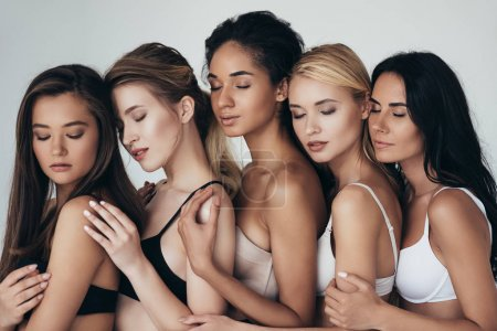 Photo pour Five sexy multiethnic girls in lingerie embracing with closed eyes isolated on grey - image libre de droit