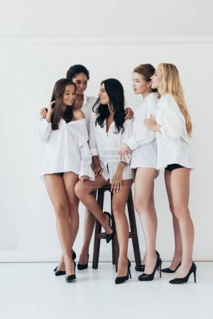 Photo for Full length view of sexy multiethnic feminists wearing heels and white shirts smiling on grey - Royalty Free Image