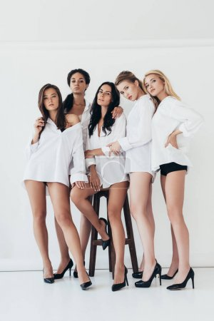 full length view of sexy multiethnic feminists wearing heels and white shirts on white