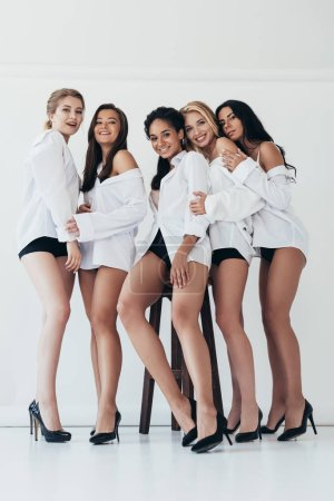 Photo pour Full length view of sexy smiling multiethnic feminists wearing heels and white shirts on grey - image libre de droit