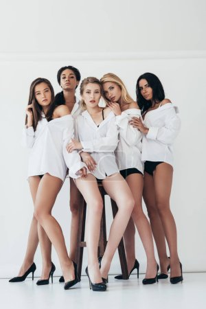 Photo for Full length view of sexy multiethnic feminists wearing heels and white shirts on grey - Royalty Free Image