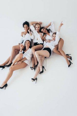 Photo pour Cinq filles multiethniques sexy portant des chemises blanches et des talons souriants et couchés sur gris - image libre de droit