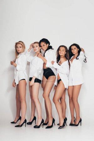 Photo pour Vue pleine longueur des féministes sexy portant des talons et des chemises blanches sur le gris - image libre de droit