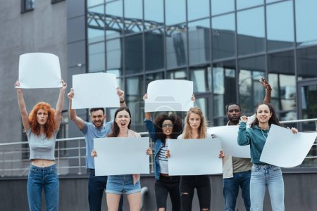 Photo for Emotional multicultural people standing with blank placards near building - Royalty Free Image