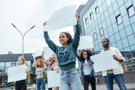Photo pour Foyer sélectif de la femme attirante retenant la plaque blanche près des personnes multiculturelles - image libre de droit