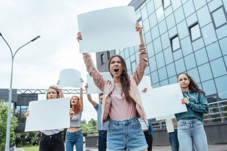 Photo for Selective focus of emotional girl holding blank placard and screaming near men and women - Royalty Free Image
