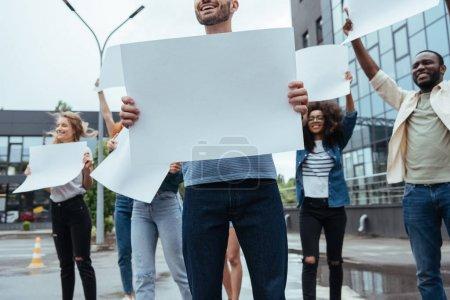 Photo pour Vue recadrée de l'homme gai retenant la plaque blanche près des personnes multiculturelles - image libre de droit