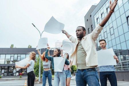 Photo pour Foyer sélectif de l'homme américain africain faisant des gestes près des filles et de l'homme sur la rue - image libre de droit