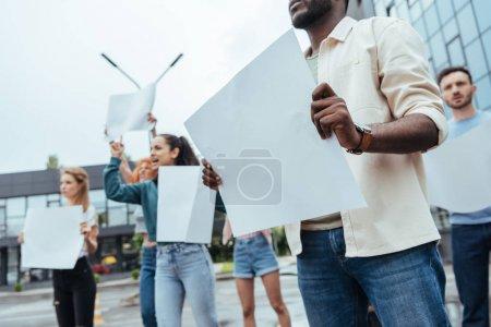 Photo pour Vue recadrée de l'homme américain africain retenant large vide près des filles et de l'homme sur la rue - image libre de droit