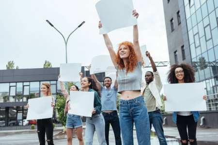Photo pour Foyer sélectif de la fille rousse retenant le conseil vide près des personnes multiculturelles - image libre de droit