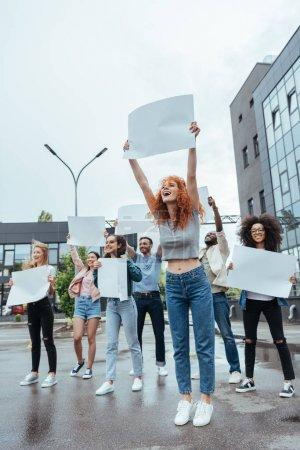 Photo pour Foyer sélectif de la fille heureuse de rousse retenant le conseil vide près des personnes multiculturelles - image libre de droit