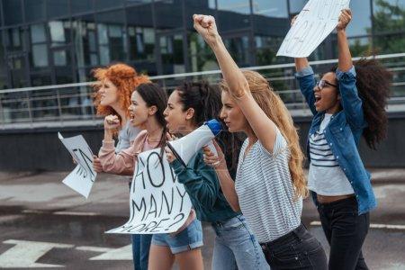 Photo pour Foyer sélectif de la fille faisant des gestes tout en tenant mégaphone près des femmes multiculturelles sur la réunion - image libre de droit