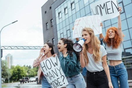 Photo for Selective focus of girl holding megaphone and screaming near multicultural women on meeting - Royalty Free Image
