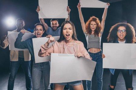 Foto de Jóvenes gente multicultural emocional gritando mientras sostiene carteles en blanco en negro - Imagen libre de derechos