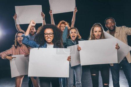 Photo pour Jeunes personnes multiculturelles criant tout en tenant des pancartes blanches sur le noir - image libre de droit