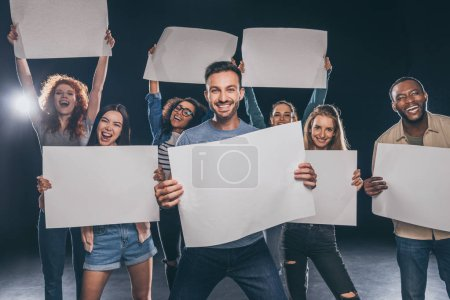 Photo for Positive multicultural people screaming while holding blank placards on black - Royalty Free Image