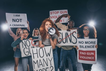 redhead girl holding placard with how many more lettering and screaming in megaphone near multicultural people on black