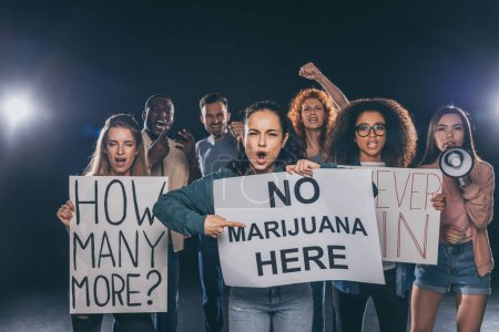 emotional girl pointing with finger at placard with no marijuana here lettering near multicultural people on black