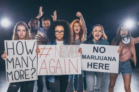 Foto de Gente multicultural emocional gritando mientras sostiene pancartas con letras en negro - Imagen libre de derechos