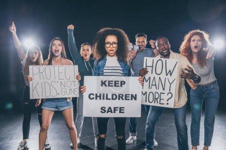 Foto de Mujer afroamericana emocional sosteniendo pancarta con mantener a los niños mensajes seguros cerca de grupo de personas en negro - Imagen libre de derechos