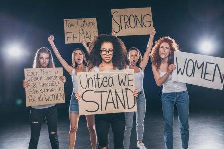 Photo pour Belles femmes multiculturelles debout et tenant des pancartes sur le noir - image libre de droit