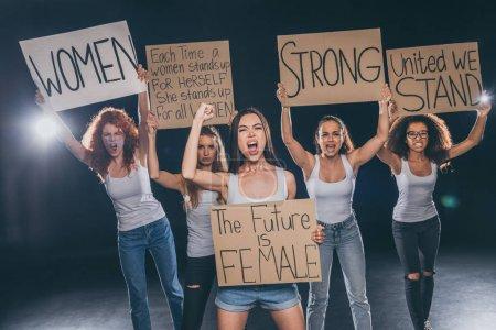 Photo pour Femmes multiculturelles émotionnelles criant et tenant des pancartes sur le noir - image libre de droit