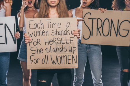 Photo pour Vue recadrée de femmes multiculturelles debout et tenant des pancartes sur le noir - image libre de droit