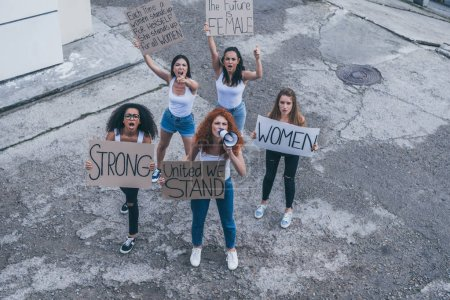 Photo for Overhead view of multicultural girls holding placards and screaming outside - Royalty Free Image