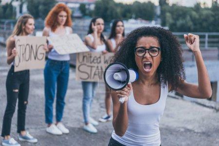 Photo pour Foyer sélectif de fille américaine africaine faisant des gestes et criant dans le mégaphone près des filles avec des pancartes à l'extérieur - image libre de droit