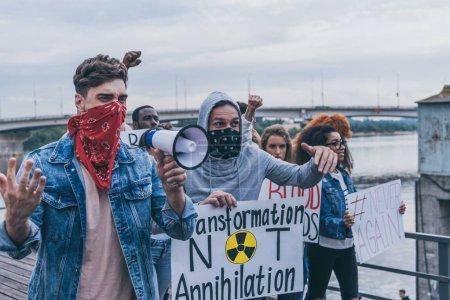 Photo pour L'accent sélectif des personnes multiculturelles émotionnelles avec le lettrage sur des pancartes marchant à l'extérieur - image libre de droit