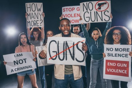 emotional african american man holding placard with guns lettering near group of people on black