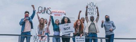 Foto de Foto panorámica de hombre con bufanda en la cara gritando en megáfono cerca de la gente multicultural con letras en carteles - Imagen libre de derechos