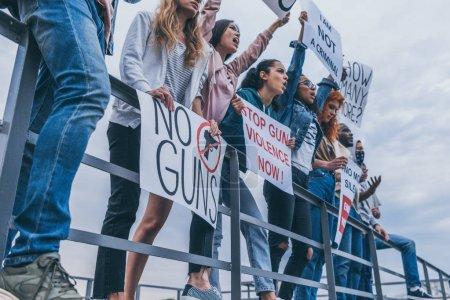 Foto de Vista recortada de la gente multicultural con letras en pancartas gritando cerca del río - Imagen libre de derechos