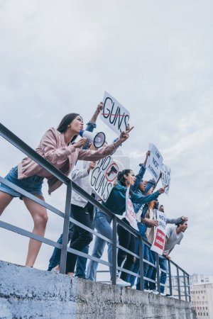 Photo for Low angle view of girl with megaphone screaming with group of multicultural people holding placards - Royalty Free Image