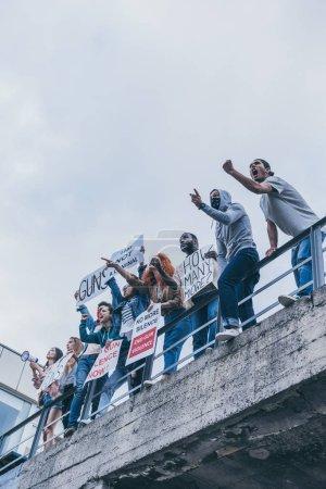 Foto de Vista de ángulo bajo de grupo multicultural de personas gritando y gesturing mientras sostiene carteles - Imagen libre de derechos