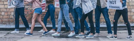 Photo for Panoramic shot of nine people walking near brick wall during protest - Royalty Free Image