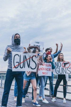 Photo pour Groupe multiculturel de personnes tenant des pancartes tout en faisant des gestes pendant la protestation - image libre de droit
